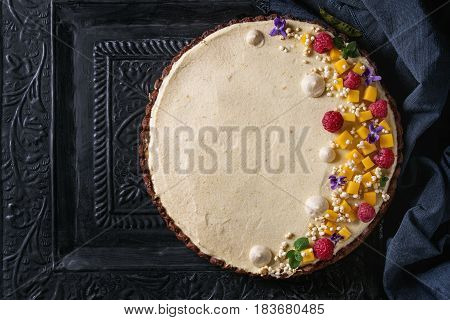 Homemade chocolate tart decorated by mango, raspberries, mint, puffed rice and edible flowers served with blue textile over dark ornate metal background. Top view. Comfort food concept.
