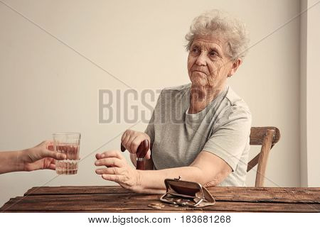 Female hand giving elderly woman glass of water. Poverty concept