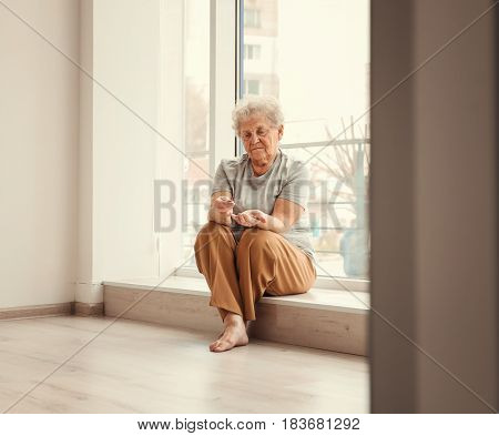 Senior woman counting coins while sitting on window sill at home. Poverty concept