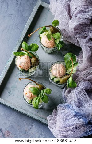 Verrines appetizer with salmon pate, red caviar, cucumber, cream cheese, herbs, capers in glasses served on wooden tray, textile gauz over blue gray texture background. Top view