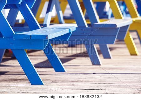 Detail view of picnic table seats in bright sunshine