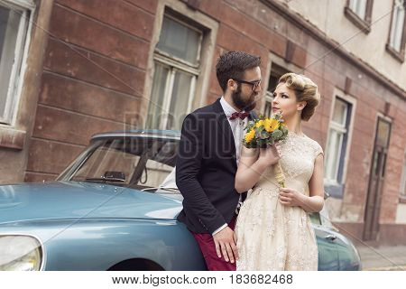 Newlywed couple standing in the cobble street next to an old retro car hugging and embarking on a honeymoon