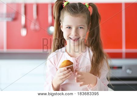 Cute little girl with tasty muffin in kitchen