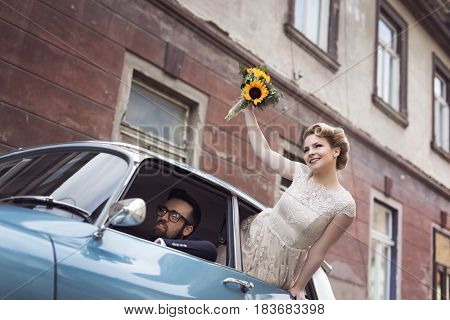 Young newlywed couple in a retro vintage car groom driving while bride is waving through a window while they are leaving on their honeymoon