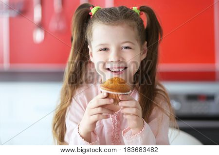 Cute little girl with tasty muffin on blurred background