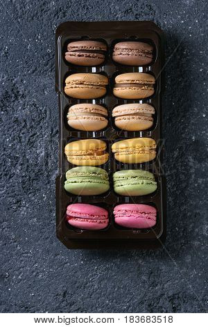 Variety of colorful french sweet dessert macaron macaroons with different fillings in balck plastic box over dark stone texture background. Top view with space