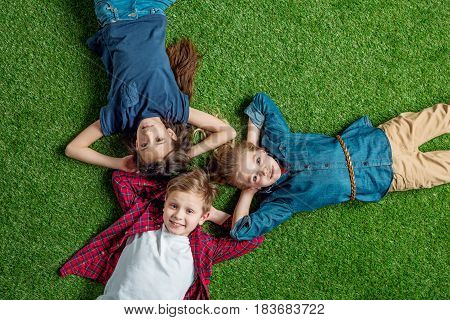 Top View Of Three Cute Kids Lying On Grass With Hands Behind Heads And Smiling