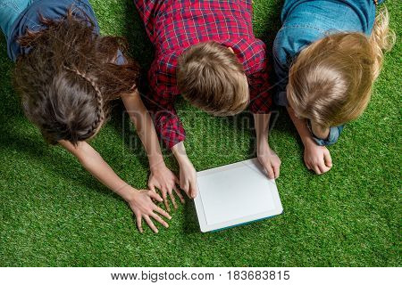 Overhead View Of Children Using Digital Tablet While Lying On Grass