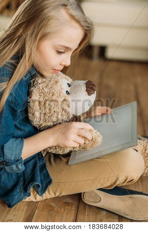Side View Of Little Girl With Teddy Bear Using Digital Tablet