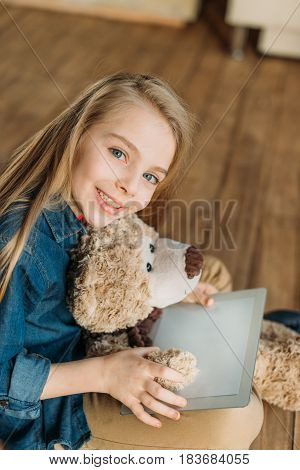 Portrait Of Smiling Little Girl With Teddy Bear Holding Digital Tablet