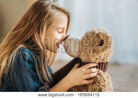 Side View Of Smiling Girl Playing With Teddy Bear