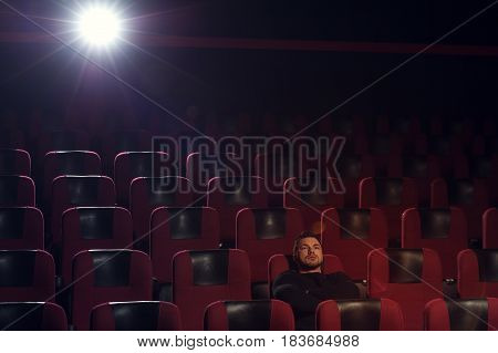 Young pensive man sitting alone in cinema theater and watching movie. Cinema, entertainment and leisure concept.