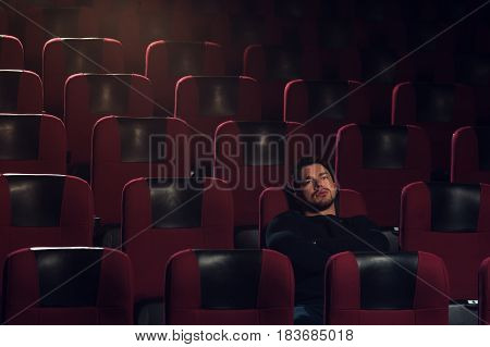 Young handsome man sitting alone in cinema theater and watching boring movie. Cinema, entertainment and leisure concept.