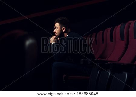 Portrait of young handsome man sitting alone in cinema theater and watching movie. Cinema, entertainment and leisure concept.