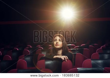 Beautiful brunette girl sitting in empty cinema theater and watching movie. Cinema, entertainment and leisure concept.