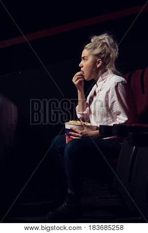 Portrait of cute blonde girl sitting in empty cinema hall, eating popcorn and watching movie. Cinema, entertainment and leisure concept.