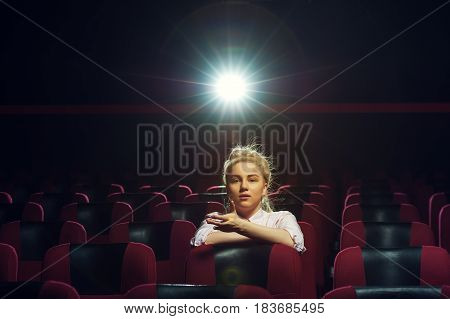 Portrait of young attractive blonde girl watching movie in cinema theater. Cinema, entertainment and leisure concept.