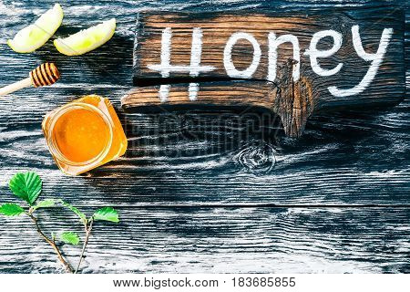 Honey jar with lemon. Black textured wood background. Wooden signboard with text 'Honey'. Top view