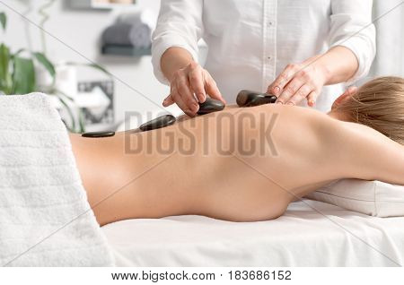 Woman Getting Hot Stone Massage In Spa Salon.