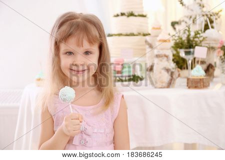 Cute little girl with tasty cake pop at party