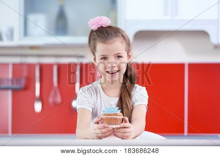 Cute little girl with birthday cake in kitchen
