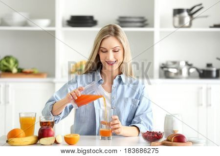 Beautiful young woman preparing fresh juice in kitchen