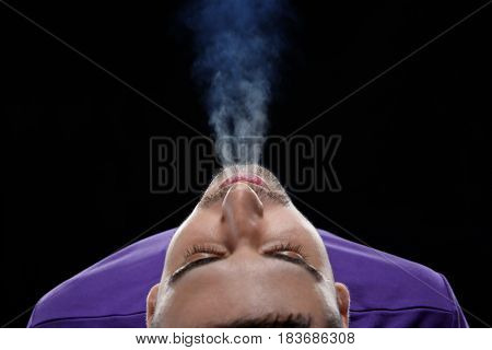 Young man exhaling smoke on black background