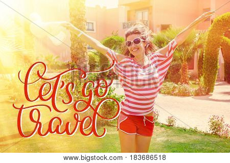 Happy young woman raising her hands in the summer park and text Lets go travel. Calligraphy lettering hand draw.