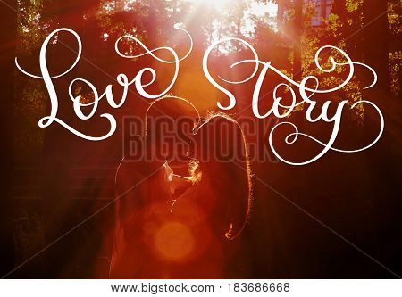Young loving couple kissing in the evening in the park opposite the sun rays and vintage text Love story. Calligraphy lettering hand draw