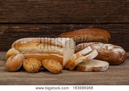 Various bread loaves on wooden background