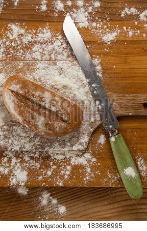 Close-up of bread loaf with knife on cutting board