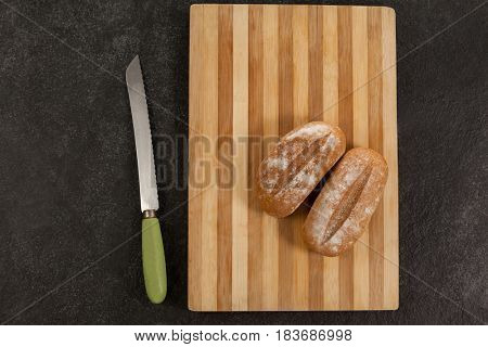 Two bread loaves on cutting board with knife