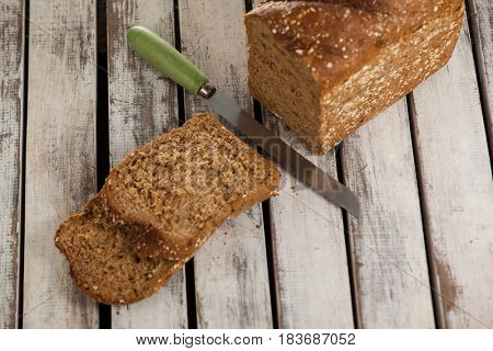 Sliced bread loaf with knife on wooden background