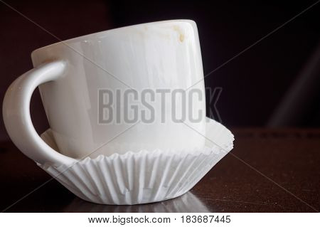 Close-up macro detail of a white espresso cup placed inside paper cupcake liners on a brown table. Coffee and cafe concept.