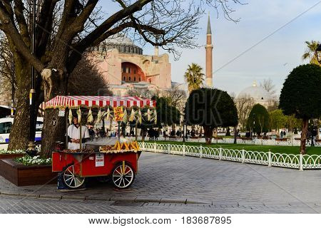 ISTANBUL TURKEY - MARCH 24 2017. Traditional red Turkey kiosk with boiled corn on March 24 2017. Seller stands near. Landmark mosque on background