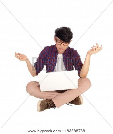 A young Asian student sitting on the floor with his laptop and is perplexed what he sees in the screen isolated for white background.