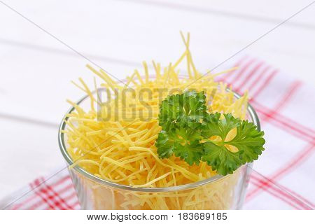 glass of dry soup noodles on checkered dishtowel - close up