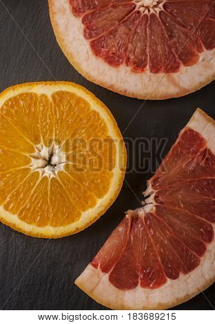 Orange and grapefruit cut close up on dark background
