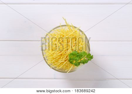 glass of dry soup noodles on white wooden background