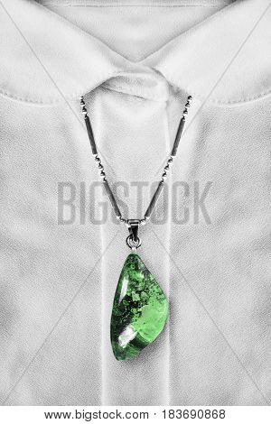 Green malachite pendant over white blouse closeup as a background