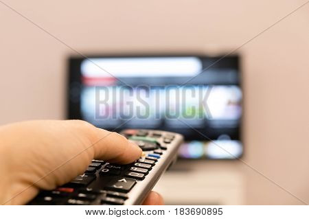 Watching TV and using remote controller. Hand holding TV remote control with a television in the background. Smart tv