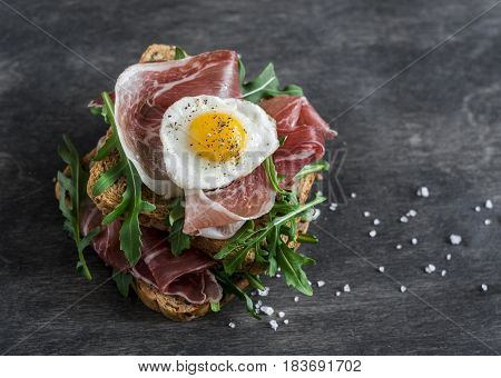 Prosciutto arugula and fried quail eggs sandwich on wooden background top view. Delicious breakfast snack or appetizer