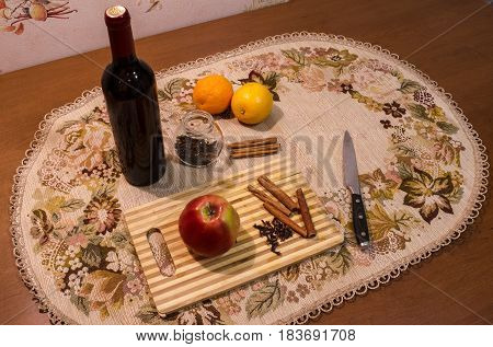 Mulled wine preparation. Red wine clove cinnamon orange and other spices on the cooking board on wooden table it kitchen.