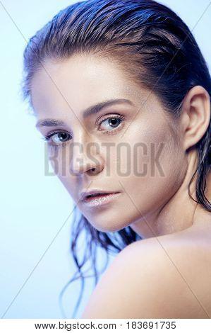 Beautiful woman face portrait close up on blue background
