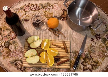 Mulled wine making. Red wine clove cinnamon sliced orange sliced apple in pot and other spices on the cooking board on wooden table it kitchen. Top view.