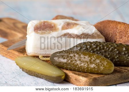 Snack. Salted cucumbers, lard and rye bread on the cutting board.