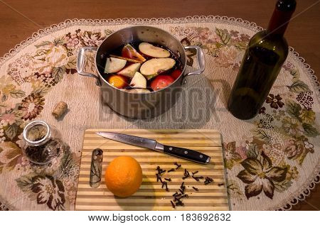 Mulled wine preparation. Red wine clove cinnamon orange sliced apple in pot and other spices on the cooking board on wooden table it kitchen.