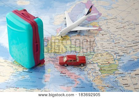 Trip or traveling by airplane concept. Miniature toy airplane, car and suitcases on map.