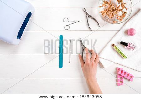 Woman Hands Care. Top View Of Beautiful Smooth Woman's Hands With Professional Nail Care Tools For Manicure On White Background. Close up. Top view. Copy space