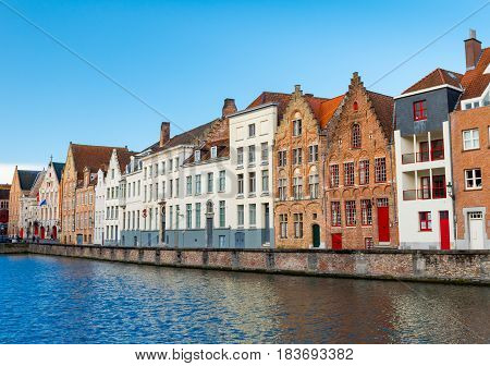 Bruges (Brugge) Belgium - February of 2016: Typical Belgian street with traditional medieval brick houses and water canal